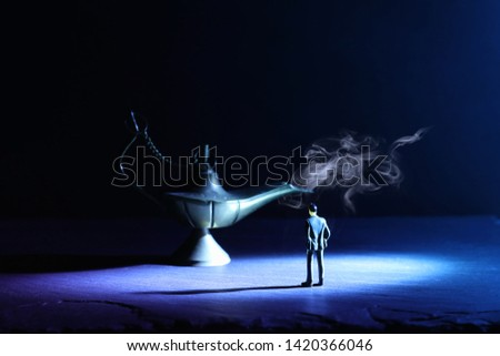 Concept picture of a businessman looking at Aladdin lamp with smoke, asking for a wish