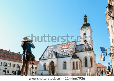 Concept picture of travel in Croatia, women is taking picture St. Mark's Church in Zagreb