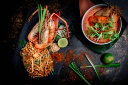 Concept pictures of famouse Thai dishes, Tom Yum Kung & Phad Thai. Beautiful presentation on black stone and black background.