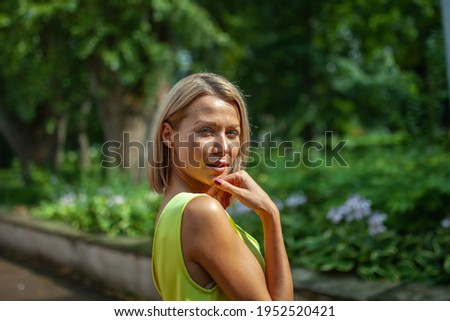 Concept portrait expressions. Young woman  outdoor portrait in city park. Looks over his shoulder straight into the camera.