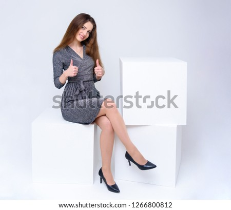 Concept portrait of a beautiful brunette girl posing sitting in the studio on a light background on a cube. Photo in full growth. Directly in front of the camera, Isolated, smile, happiness.