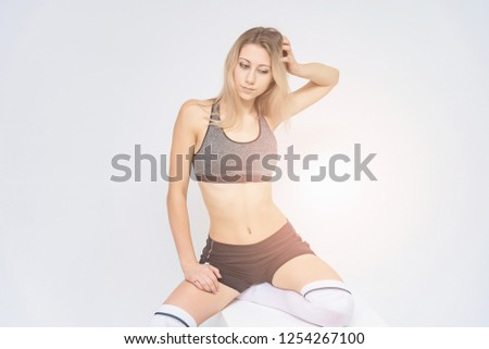 Concept portrait of a beautiful fitness girl blonde smiling on a white background advertisement. #1254267100