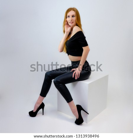 Concept portrait of a pretty beautiful red-haired girl talking on a gray background in the studio sitting on a cube in front of the camera. They show different emotions in different poses.