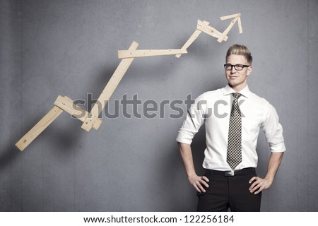 Concept: Positive business outlook. Smiling confident businessman with business vision in front of upwards pointing business graph, isolated on grey background.
