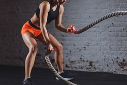 Concept: power, strength, healthy lifestyle, sport. Powerful woman do workout with battle ropes in gym