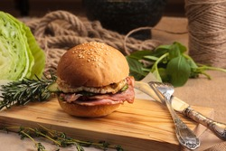 Concept: restaurant menus, healthy eating, homemade, gourmands, gluttony. Trendy breakfast burger with ham and eggs with ingredients on messy vintage wooden background.