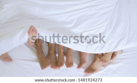 Concept Sex clubs, swing clubs, lifestyle clubs, formal, informal groups. feet of a group of people under a white blanket on a white sheet on a king size bed