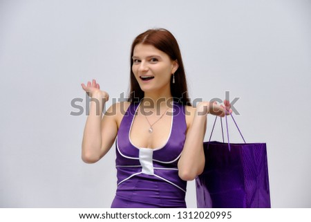 Concept shopping studio Portrait of a young beautiful brunette girl standing on a white background with packages from the store. She is directly in front of the camera in various poses.