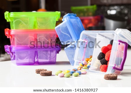 Concept shot made of transparent colorful plastic food containers on kitchen worktop with colorful candies in singles and bills