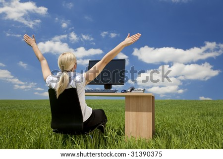 Concept shot of a young woman sitting at a desk in a green field raising her arms into a blue sky with fluffy white clouds. Shot on location. #31390375