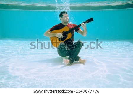Concept shot of young man looking for solitude and tranquility for inspiration and music creation. Musician playing guitar underwater. Concept of censorship, isolation and solitude. #1349077796
