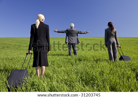 Concept shot showing three business executives, one male and two female, walking through a green field towards the horizon. Environmental, business and travel concepts, shot on location.