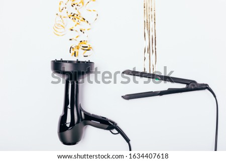 Concept styling different types of hair, curly and straight. Hairdryer and straightener next to stylized golden strands on white background, flat lay.