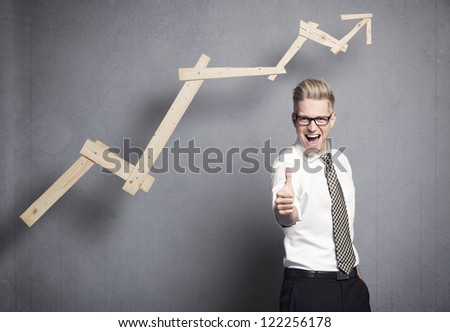 Concept: Success in business. Confident young businessman holding thumb up in front of ascending business graph, isolated on grey background.