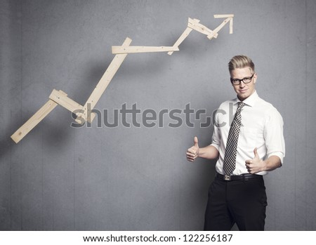 Concept: Successful business. Confident young businessman holding thumbs up in front of positive business graph, isolated on grey background.