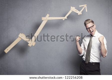 Concept: Successful business. Energetic young businessman cheering in front of ascending business graph, isolated on grey background.