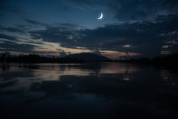Concept the crescent moon the symbol of Islam begins the eid al Fitr. Seeing the moon in the night sky. The evening sky and the vast river in darkness are beautiful.