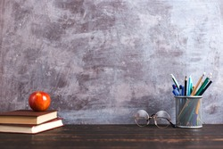 Concept to teacher's day. Pens, apple, pencils, books and glasses on table. Back to school, copy space.