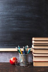 Concept to teacher's day. Pens, apple, pencils, books and glasses on the table, against the background of chalkboard. Back to school, copy space.