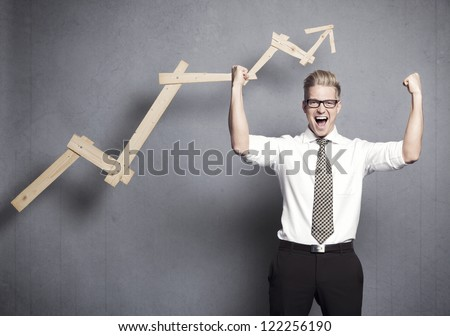 Concept: Triumph in business. Strong young businessman cheering in front of upwards pointing business graph, isolated on grey background.