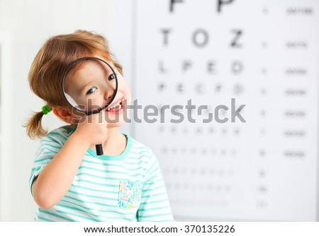 concept vision testing. child girl with a magnifying glass at the doctor ophthalmologist