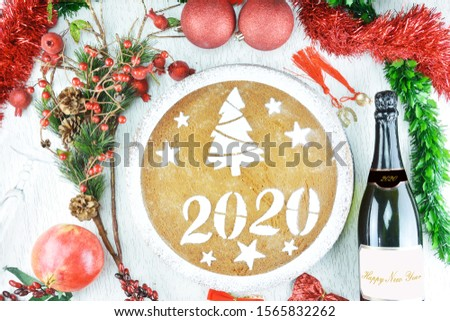 Concept with traditional Greek new year's cake,vasilopita, a bottle of champagne,a class ,a pomegranate,ornaments and lucky charms
