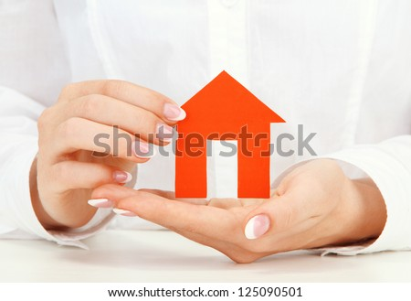 concept: woman hands with paper house, close up - stock photo
