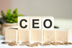 Concept word CEO on wooden blocks on beautiful background from green flower. The word CEO on wood cubes with coins and calculator on the background. Business concept. CEO - Chief Executive Officer