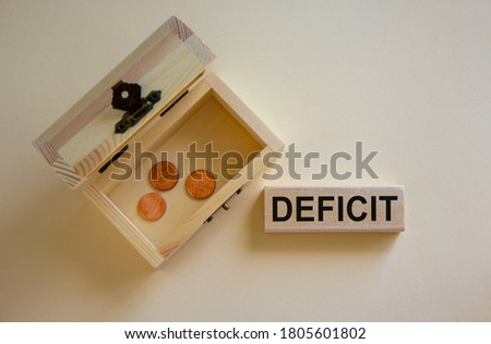 Concept word 'deficit' on wooden block on a beautiful white background, small chest with coins. Business concept, copy space. Foto stock ©