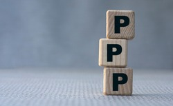 concept word PPP on wooden cubes on a gray background. Technology concept