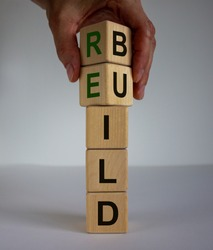 Concept word 'rebuild' on cubes on a beautiful wooden table. Male hand. White background. Business concept. Copy space.