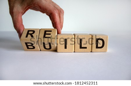 Concept word 'rebuild' on cubes on a beautiful wooden table. Male hand. White background. Business concept. Copy space. Stockfoto ©
