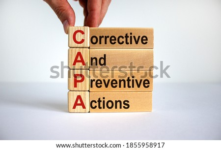 Concept words 'CAPA, corrective and preventive actions' on cubes and blocks on a beautiful white background. Male hand. Business concept. Copy space. Stock fotó ©