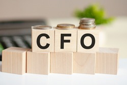 Concept words CFO on wooden blocks on beautiful background from dollar bills. The word CFO on wood cubes with coins and calculator on the background. Business concept. CFO - Chief Financial Officer