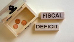 Concept words 'fiscal deficit' on blocks on a beautiful white background, small chest with coins.