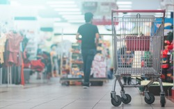 Conceptimage of buying. Image containing shopping cart in a mall with a copy space over blurry background and leading lines