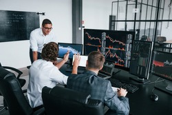 Conception of teamwork. Team of stockbrokers works in modern office with many display screens.