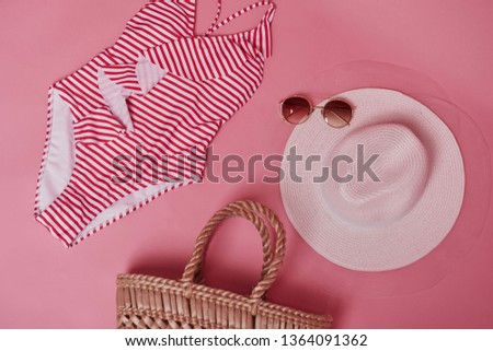 Conception of traveling and vacations. Bikini on the pink colored table. Group of objects for the traveling and vacations. #1364091362
