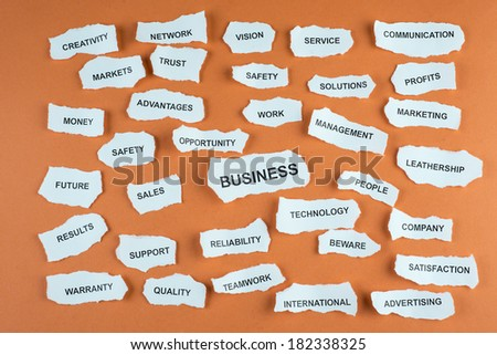 Concepts about business written on scraps of paper with an orange background