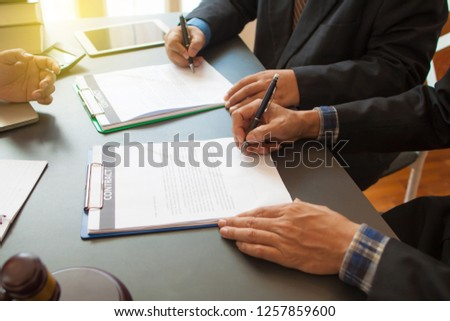 Concepts about contracting, legal agreements, lawyers and businesses. Two businessmen covenant to buy / sell products in advance. To sign a mutual agreement. #1257859600
