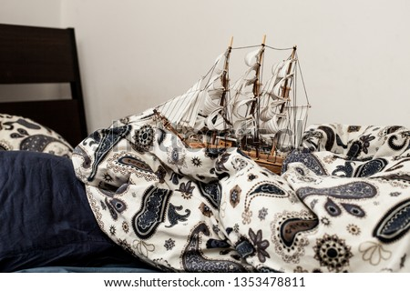 Concepts of business and creativity. model of a sailing ship in a bed with a carelessly crumpled blanket and pillows in blue bedding. symbolism and abstraction #1353478811