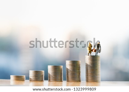 Concepts of retirement planning and finanacial. Miniature people: Old couple figure standing on top of coin stack.  #1323999809