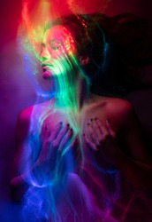 Conceptual avant-garde portrait of a beautiful young girl covered with multicolored lines applied by a light brush. Art style creative photo. Advertising, fashion and commercial design