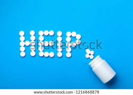 Conceptual background on the medical topic the word Help laid out from white  round pills on