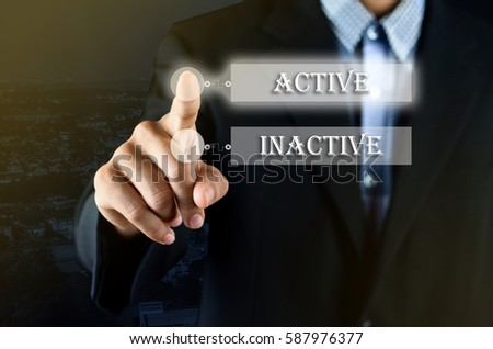 Conceptual - Business man pointing his hand choosing on transparent screen with option between Active or Inactive