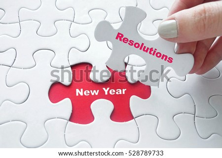 Conceptual: Close up of girl's hand placing the last jigsaw puzzle piece with word New Year Resolutions #528789733