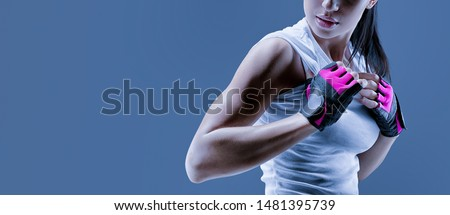 Conceptual close up portrait of fitness athletic young female model in sports clothing showing her well trained body Confident female bodybuilder with power hand in gloves over toned blue background