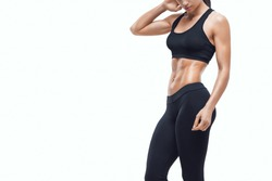 Conceptual close up portrait of fitness athletic young woman in black sportswear clothing showing her well trained body Confident female fit bodybuilder isolated on white Copy free space Clipping path