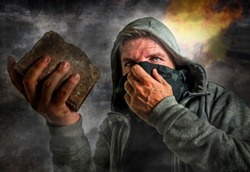 conceptual composite of radical and violent man . furious antifa and ultra protester with face mask throwing brick on street riot chaos in fire and smoke in anarchy and revolution concept