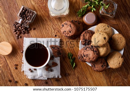 Conceptual composition with two jars of coffee beans, instant coffee and tasty cookies on wooden table, selective focus